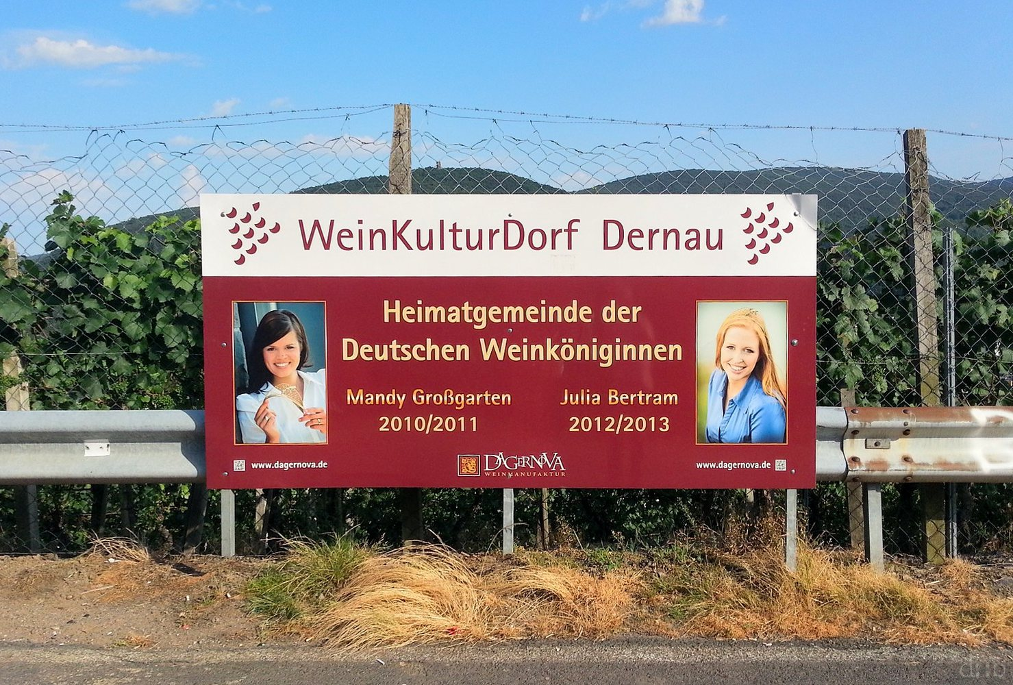 "A billboard explains that Dernau is ""home to the German wine queens"" who are named below."