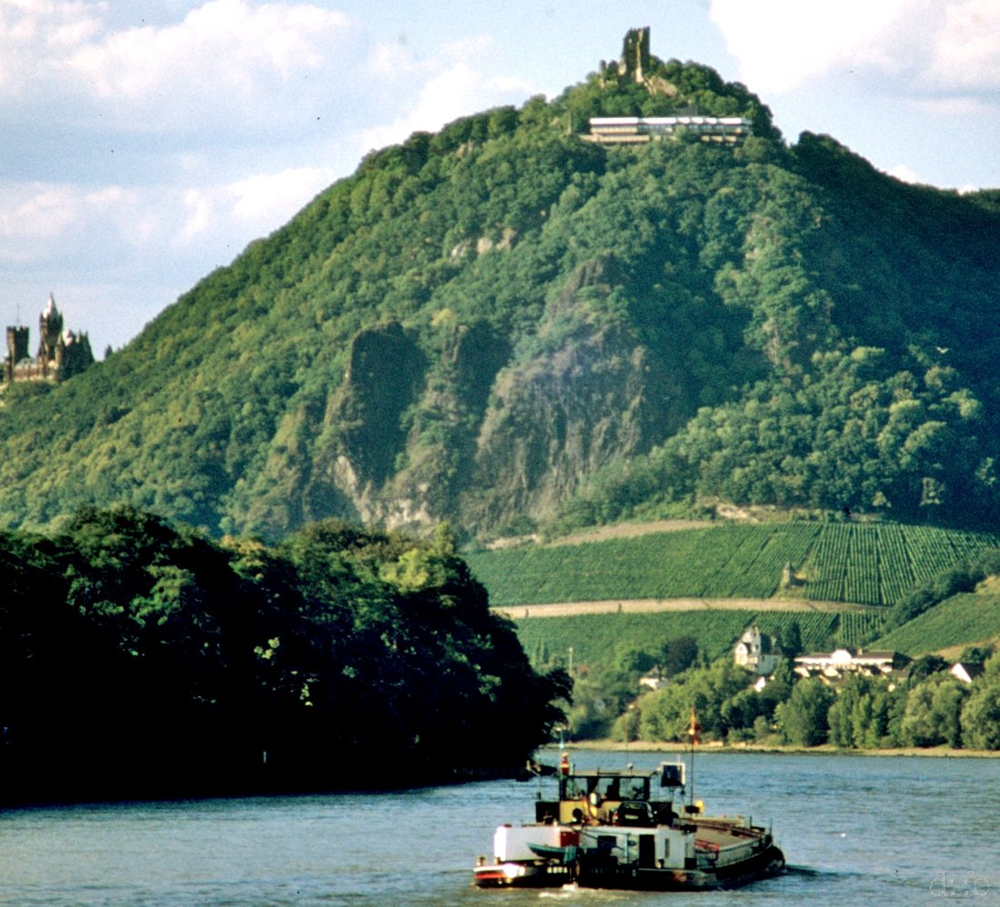 A cargo ship is riding downstream the river Rhine, passing Königswinter with the Drachenfels and the Hirschburg in the background.