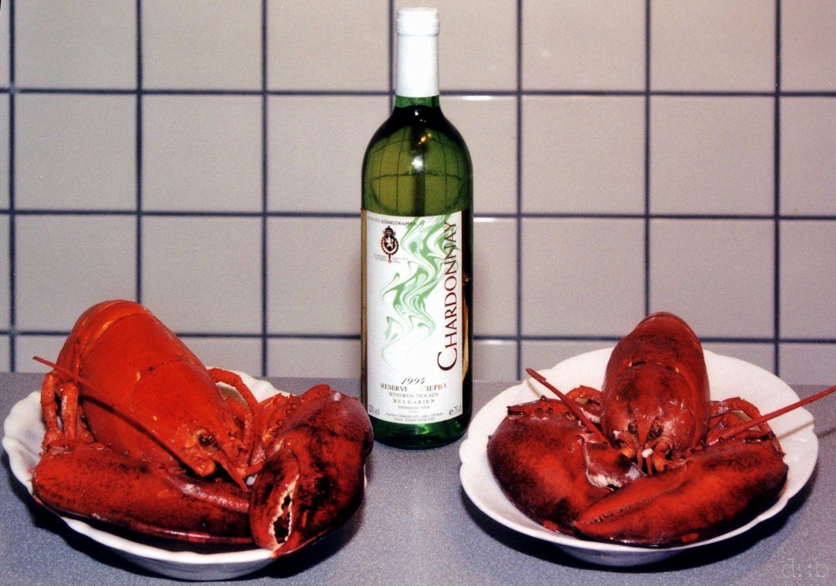 Two lobster dishes, accompanied by a bottle of white wine.