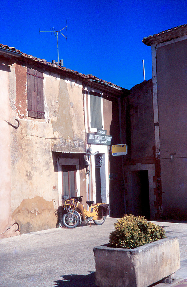 A motobike standing in front of a closed countryside postal office in southern France.