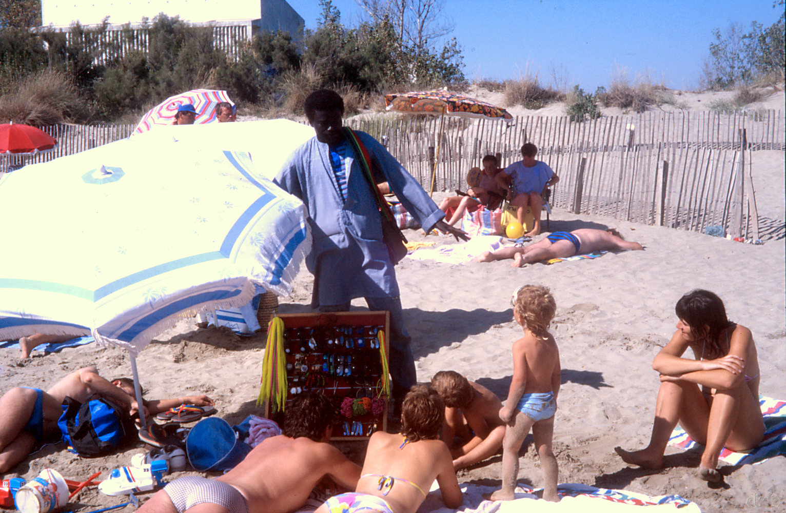 A flying merchant offers his goods to people on the beach.