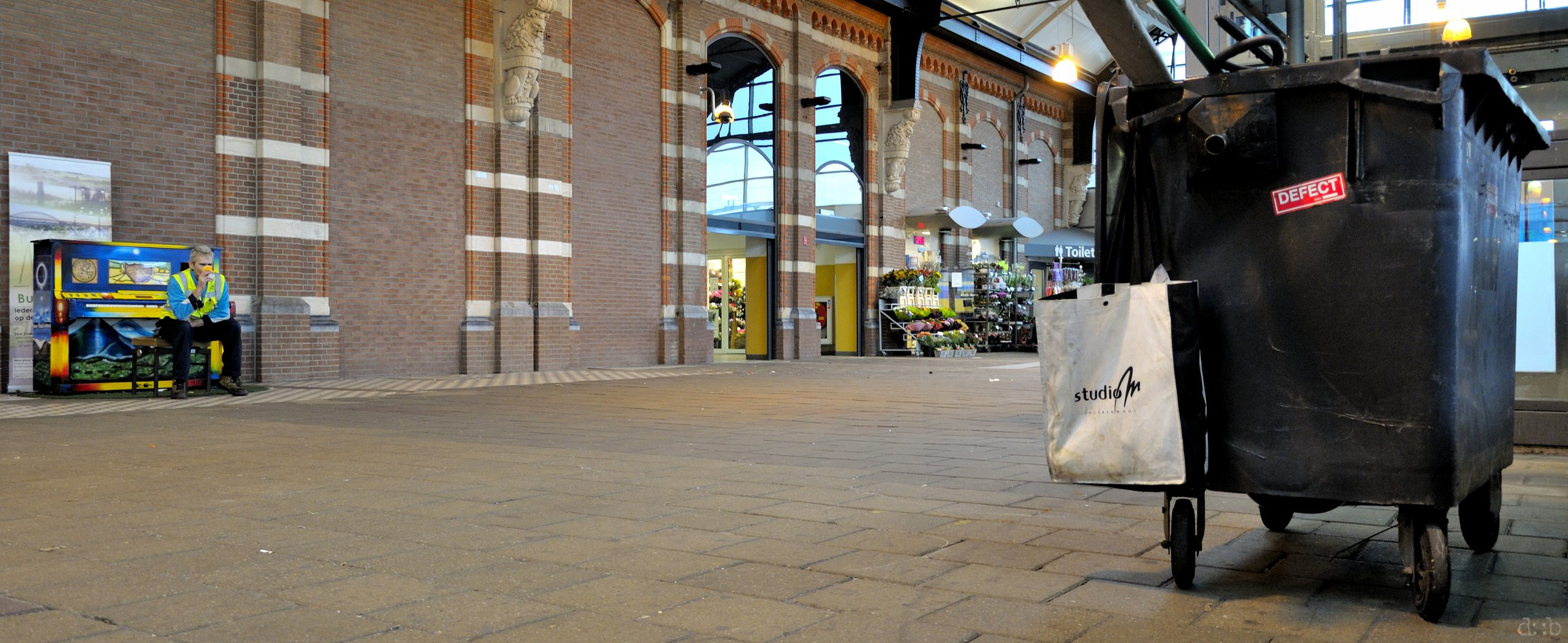 A cleaning guy taking a coffee break at the public piano at Nijmegen central station