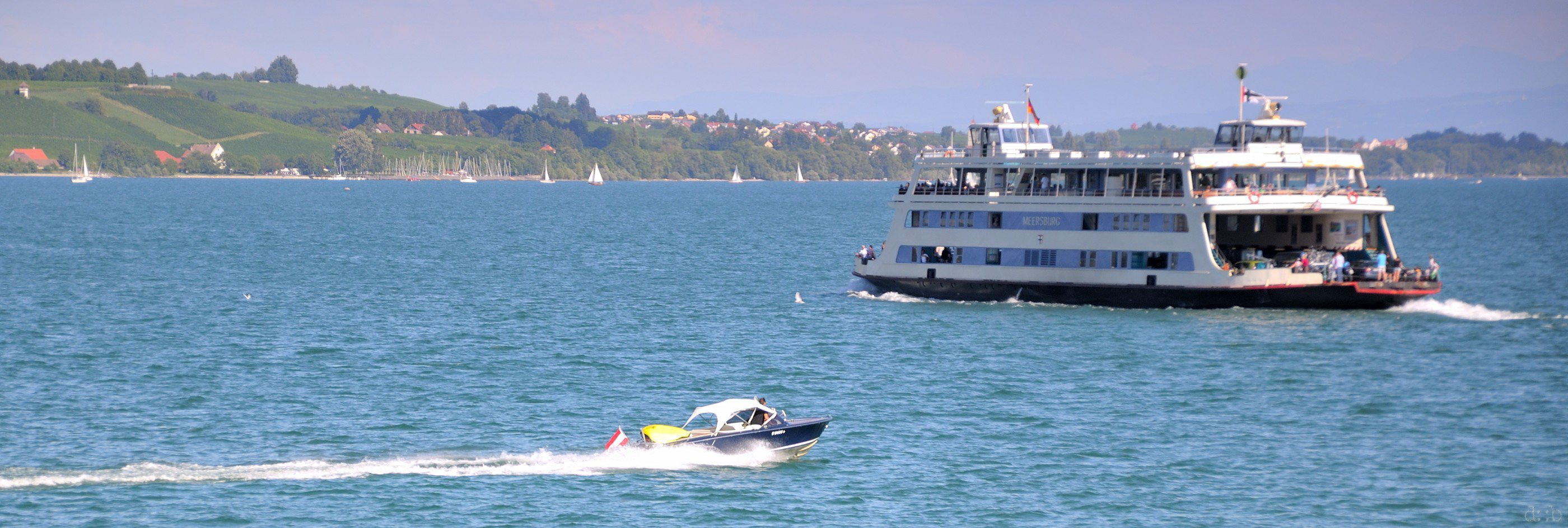 A sports yacht meets a ferry on Lake Constance near Friedrichshafen.