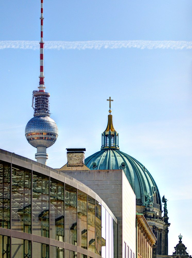 Berlin's television tower and a condensation trail compete with the cathedral in terms of the largest cross