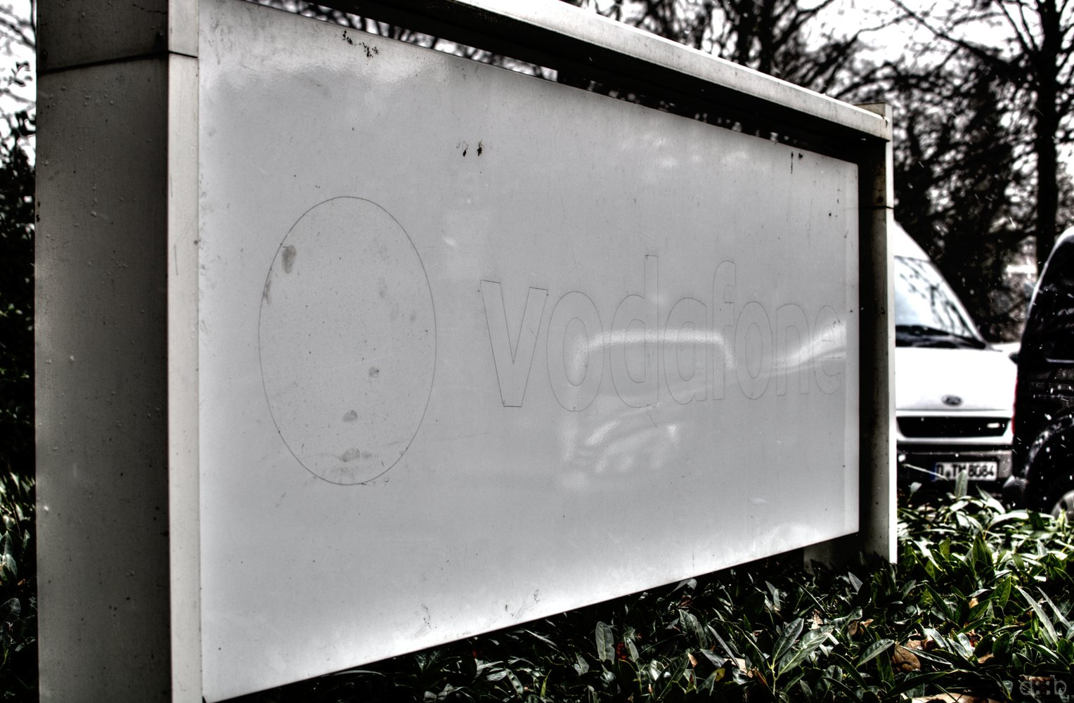 A former company sign, still showing outlines from the removed Vodafone logo