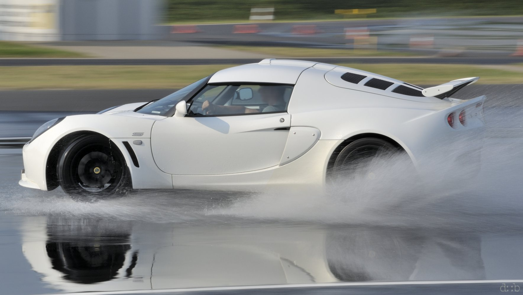 A white Lotus Exige is sliding through an artificial water puddle