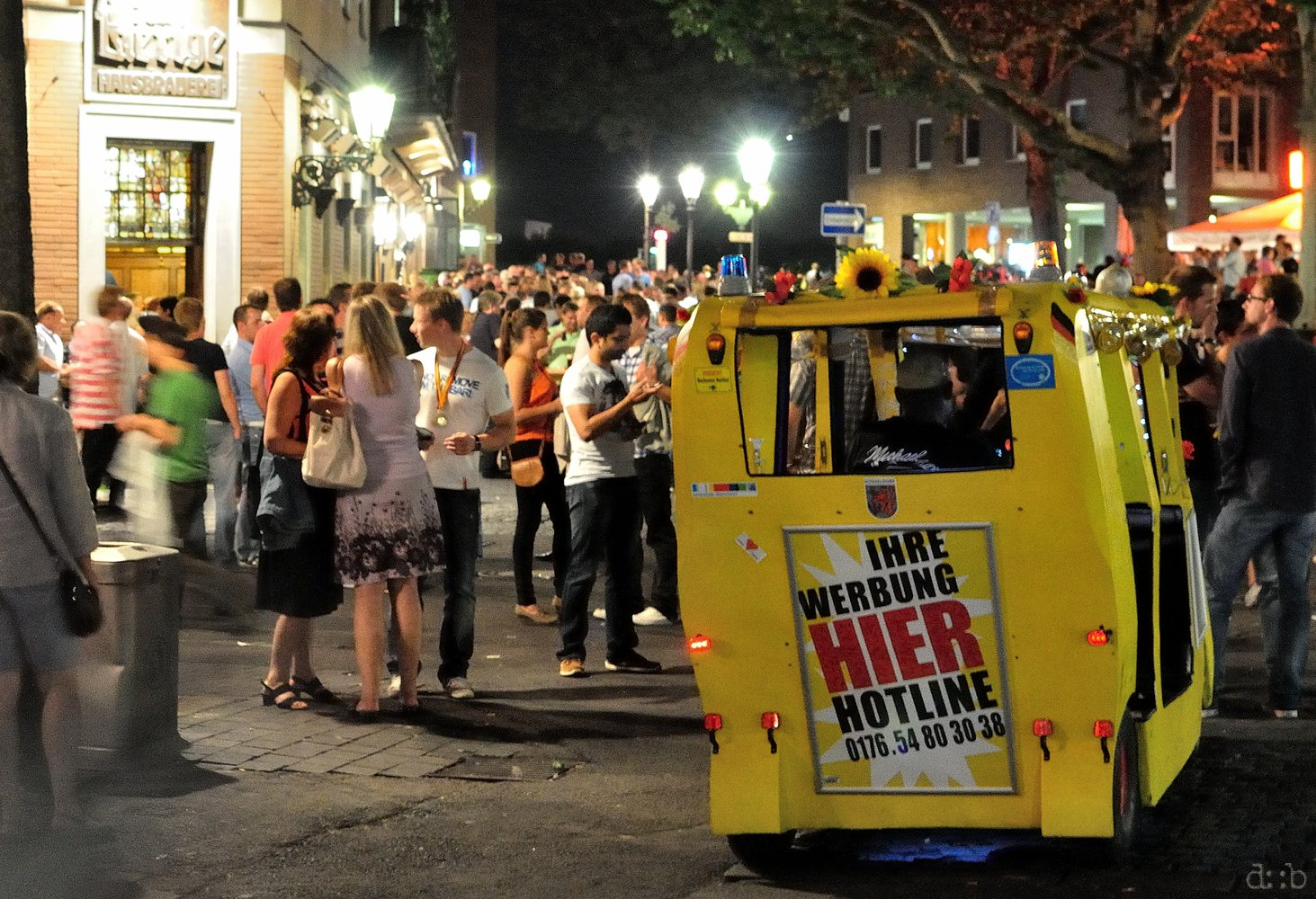 A caddy cab is waiting for passengers right in the crowd before a crafts brewery.