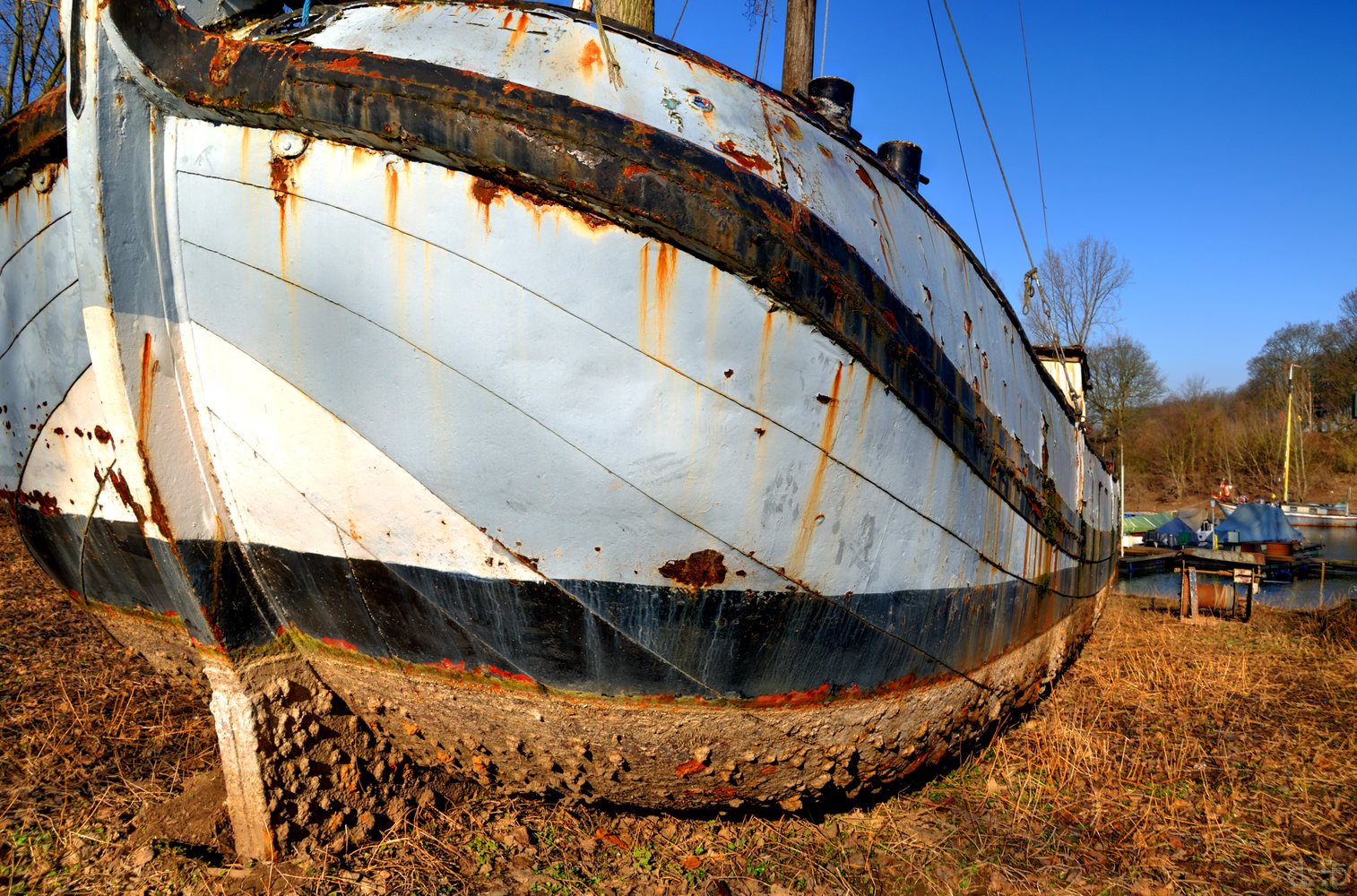 A vintage boat, lying dry outside the harbor.