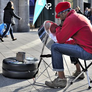 A musician taking a break from his playing the steel drum on Kurfürstendamm, Berlin, Germany.