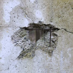 An eye-like hole in a concrete wall, surrounding former military facilities of the then-GDR.