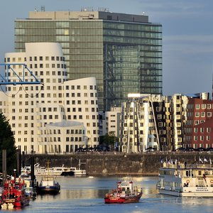 Boat traffic in front of Düsseldorf's Medienhafen, with its fancy architecture, and the Stadttor in the background.