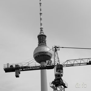 Berlin's Alexanderplatz television tower, with a construction crane at its side