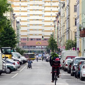 Perspective view through a street with historic buildings onto a (once) futuristic apartment building in Kreuzberg