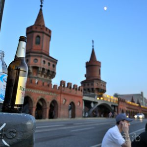 Evening scene on Berlin's Oberbaumbrücke, with beer bottles and an U-Bahn train