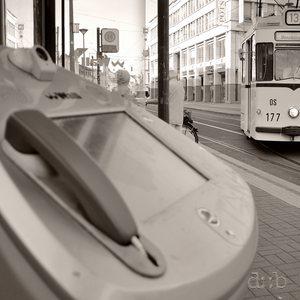 A historic tramway train turns around a corner, facing a public internet terminal