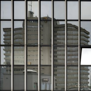 A 1970's office building reflects in another one's windows