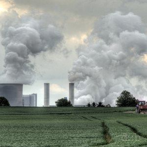 A tractor on its duty with a smoking power plant in the background
