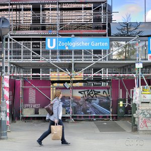 Berlin subway station U-Bahnhof Zoologischer Garten during construction works. A woman with shopping bags rushes by a man who is searching a garbage bin, probably for returnable bottles.