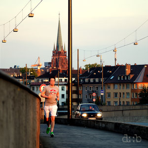 A jogger climbs the ramp to one of Düsseldorf's Rhine bridges, as does a car next to him.