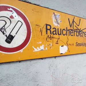 "A sign designates an inviting smokers' area at Wuppertal's (""central"") Elberfeld station."