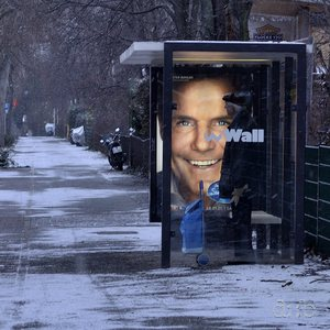 "An advertisement for the German branch of ""Pop Idol"" enlightens a winterly bus stop"