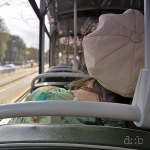 A tram passenger is taking a nap during her ride